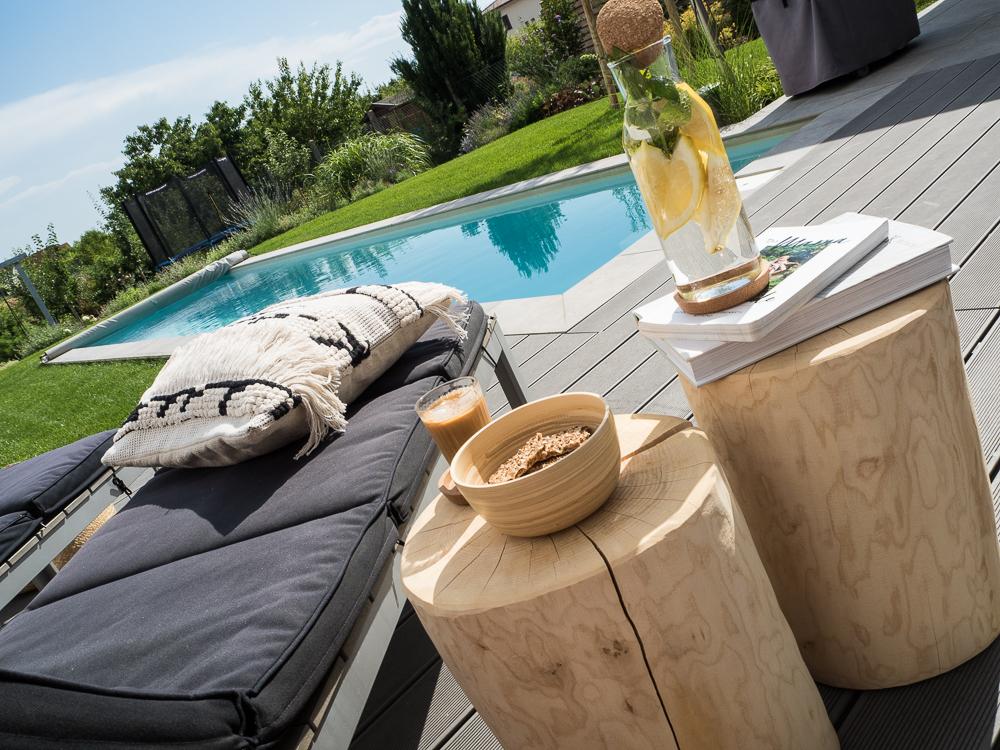 Terrassen-Gestaltung-Sonnenliege-Pool-Holzstämme-mit-Getränken-und-Snacks